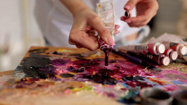 Artista-exprime-la-pintura-del-tubo-en-la-paleta-de