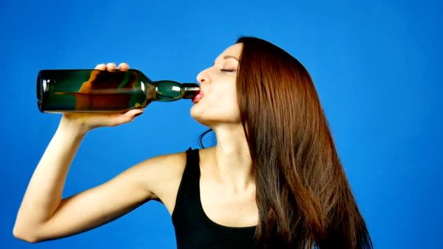Morena-joven-sexy-caliente-bebiendo-vino-del-cuello-de-una-botella-Mujer-borracha-problema-con-el-alcohol-depresión-problemas-psicológicos-su-tratamiento-y-prevención