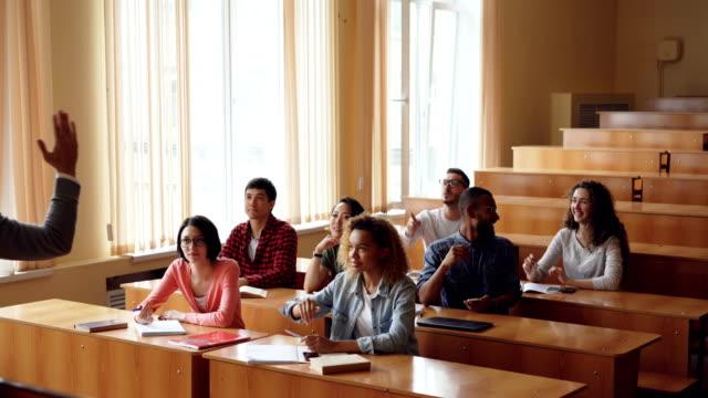 Freundlich-fröhlich-Lehrer-bärtigen-Mann-stellt-Fragen-wissen-überprüfen-während-Studenten-Hände-erhebend-sind-und-Beantwortung-junge-Menschen-glücklich-sind-Wenn-richtige-Antwort-gibt-