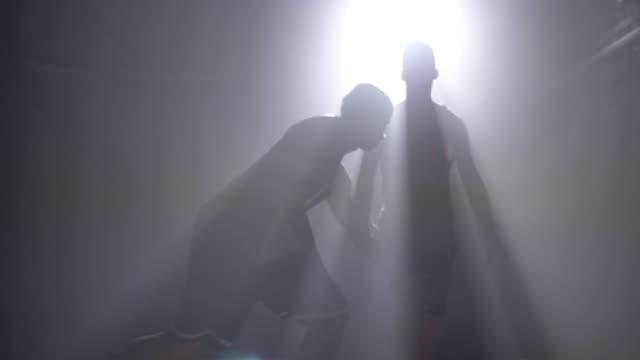 Silueta-de-jugadores-de-baloncesto-dos-uno-a-uno-en-la-habitación-jugando-con-humo-y-con-iluminación