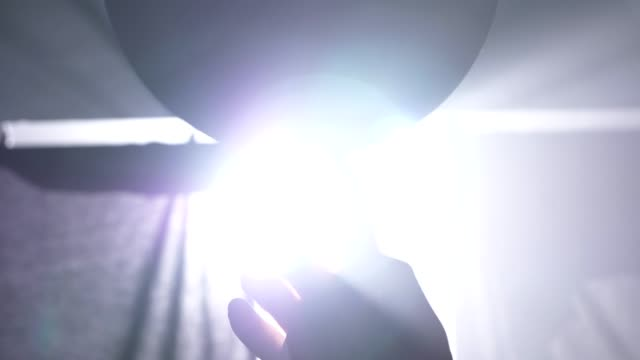 Close-footage-of-basketball-player-spinning-ball-on-his-finger-dark-misty-room-with-floodlight