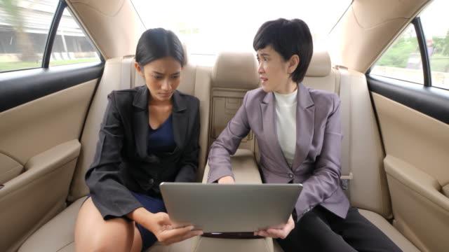 Empresaria-que-reprimenda-de-su-jefe-femenino-en-el-asiento-trasero-de-un-coche
