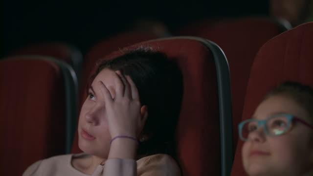 Teenager-Mädchen-Film-im-Kino-mit-jüngeren-Schwester