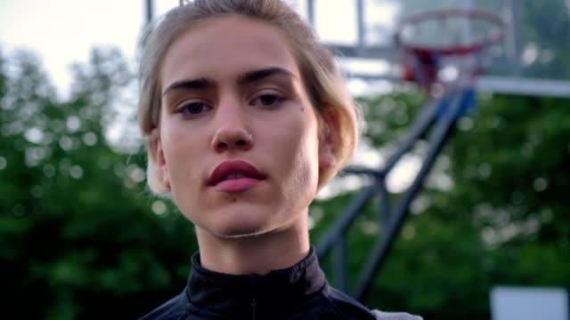 Retrato-de-mujer-hermosa-segura-jugando-con-baloncesto-y-mirando-a-cámara-en-parque-aro-en-fondo