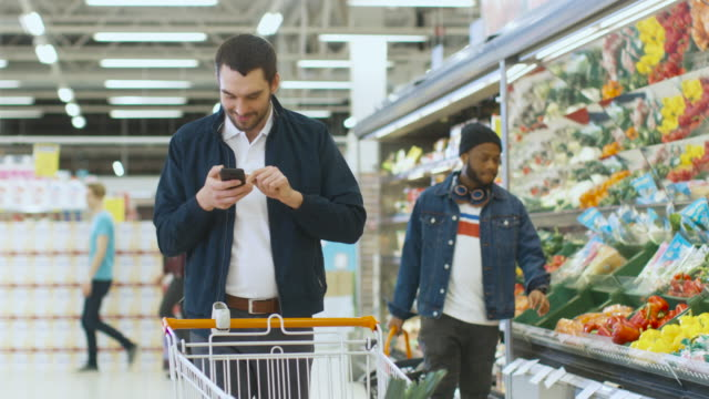 At-the-Supermarket:-Handsome-Man-with-Smartphone-Smiles-Walks-Through-Fresh-Produce-Section-of-the-Store-Picks-up-Vegetables-and-Throughs-into-Shopping-Cart-