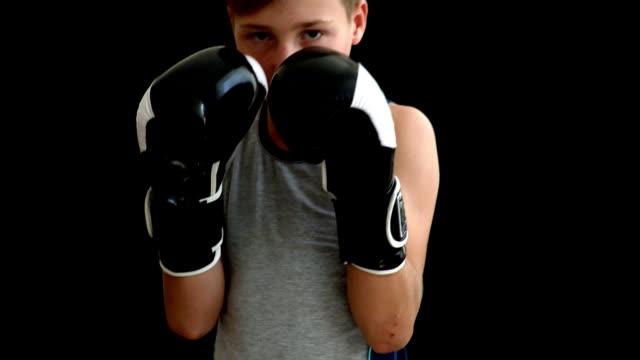 Ein-Teenager-steht-in-Boxhandschuhen-auf-einem-dunklen-Hintergrund.-Der-Junge-hat-schwarze-und-weiße-Handschuhe,-die-fast-sein-Gesicht-abdecken.-Der-junge-ist-in-einer-grauen-Jersey-gekleidet,-hat-blondes-Haar-und-dunkle-Augen