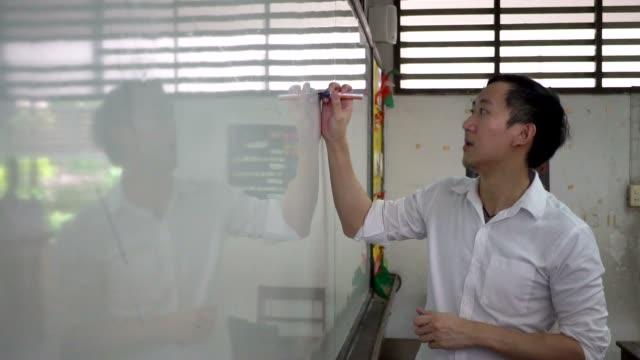 Joven-profesor-Asia-dando-una-lección-en-el-aula--