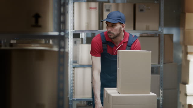 Warehouse-Worker-Collects-Order-by-Taking-Cardboard-Boxes-and-Parcels-of-the-Shelf-and-Putting-them-On-a-Trolley-
