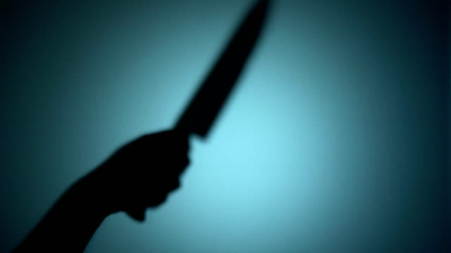 Killer-slashing-victim-with-a-knife-spooky-silhouette-behind-the-glass-murder