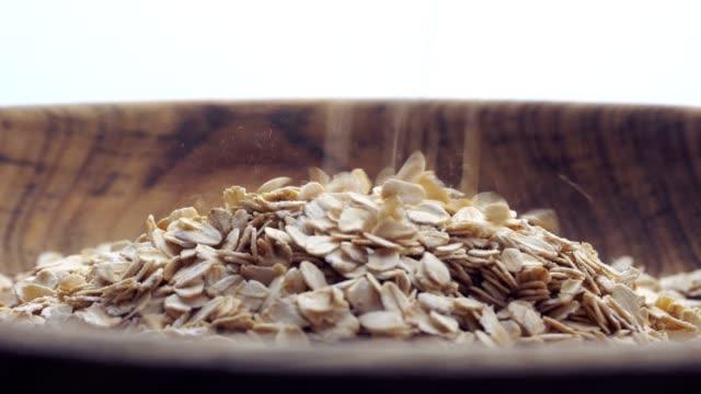 Slow-motion-closeup-oat-flakes-falling-into-bowl