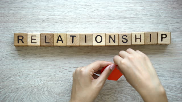 Relationship-word-on-wooden-cubes-female-hands-tearing-paper-heart-in-half
