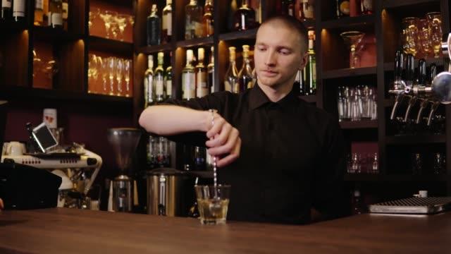 Joven-barman-en-la-barra-interior-vertiendo-whisky-en-cristal-y-trayendo-para-los-visitantes