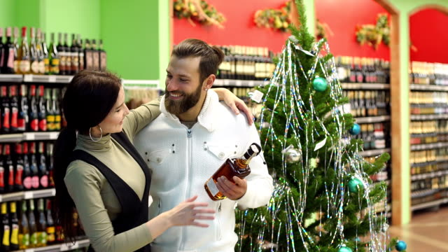 Happy-couple-buying-cognac-in-a-shop-standing-near-a-decorated-Christmas-tree-