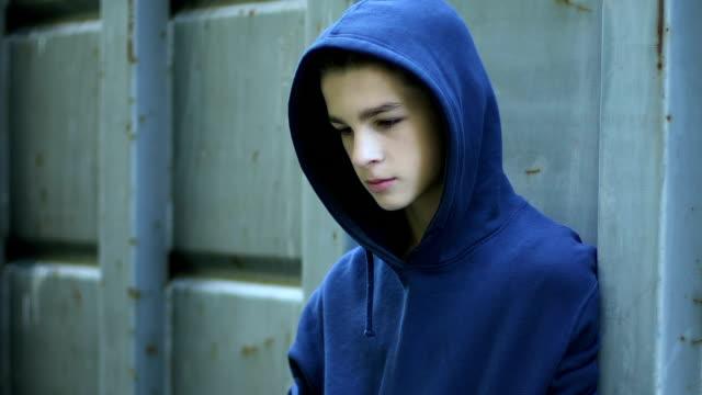 Upset-pallid-boy-hiding-behind-fence-victim-of-bullying-underage-drug-addict