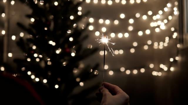 Bengala-de-mano-con-celebrar-el-fondo-de-luces-de-Navidad