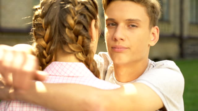 Sad-boyfriend-embracing-teen-girlfriend-and-looking-into-camera-difficulties