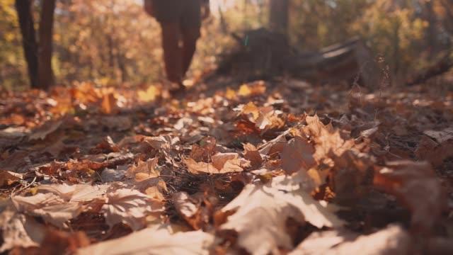 Mann-ist-Laub-close-up-der-Füße-treten-verstärkt-auf-Boden-im-herbstlichen-Wald