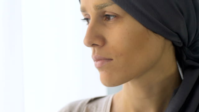 Upset-cancer-patient-looking-out-window-weakened-and-depressed-after-chemo