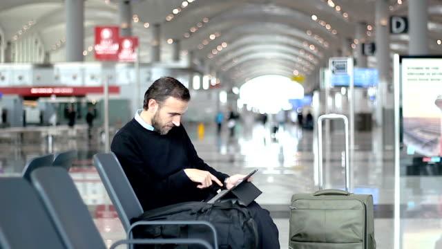 Pasajeros-utilizando-su-tableta-en-el-salón-de-la-salida-en-el-aeropuerto