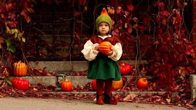 Funny-little-girl-in-a-gnome-costume-holds-a-pumpkin-in-x-s-hand-and-looks