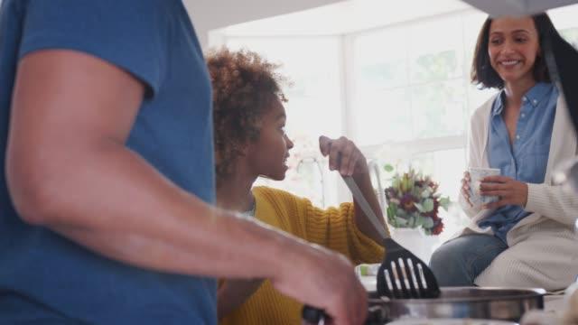 Gemischte-Renneltern-und-ihre-vor-Teenager-Tochter-bereiten-gemeinsam-Essen-in-der-Küche-hautnah