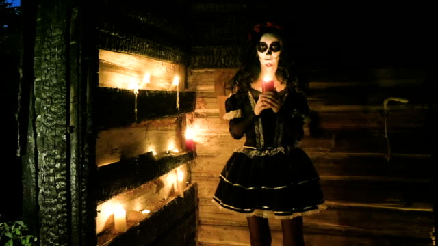 Young-woman-with-scary-skeleton-Halloween-make-up-holding-a-lighted-candle-HD