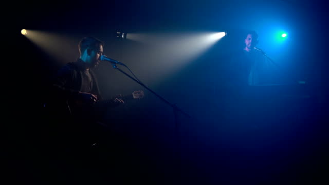 Dos-músicos-cingen-al-micrófono