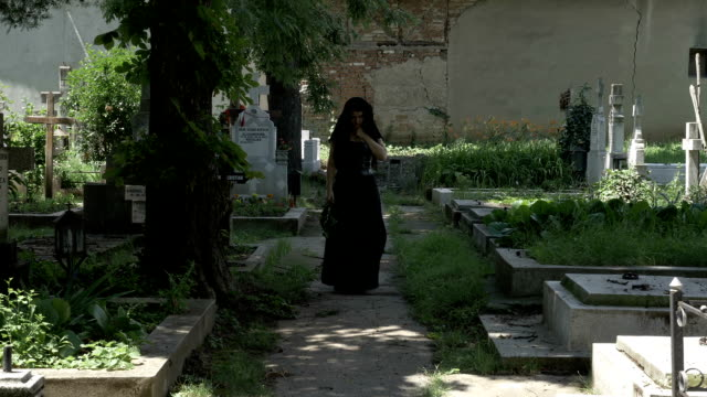 Grieved-widow-filled-with-sorrow-leaving-from-departed-husband-grave-walking-in-cemetery-alley