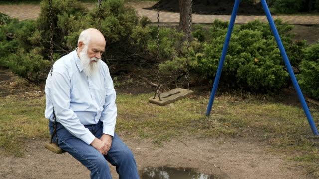 Depressive-senior-man-on-the-swing