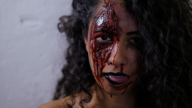 Scary-portrait-of-young-girl-with-Halloween-blood-makeup-Beautiful-latin-woman-with-curly-hair-looking-into-camera-in-studio-Living-dead-greasepaint-Slow-motion
