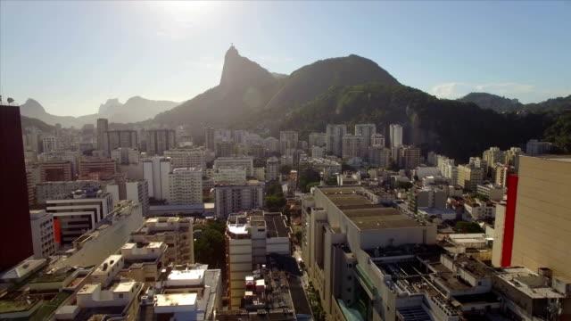 Rio-de-Janeiro-aéreo:-mover-lateralmente-a-través-de-playa-Botafogo-con-Cristo-Redentor-en-el-fondo-y-edificios-de-gran-altura-en-primer-plano-cercano