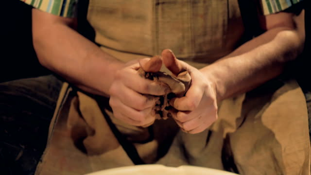 Strong-potters-hands-knead-a-piece-of-clay-