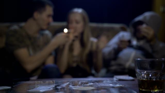 De-drogas-adictos-jóvenes-con-cocaína-en-la-mesa