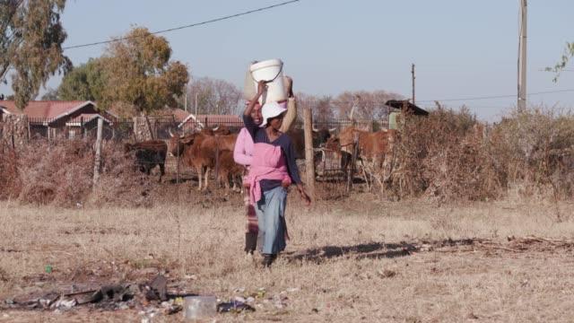 Tres-mujer-africana-llevando-agua-en-la-cabeza-en-cubos-de-plástico-de-un-origen-remoto-y-caminando-hacia-sus-casas