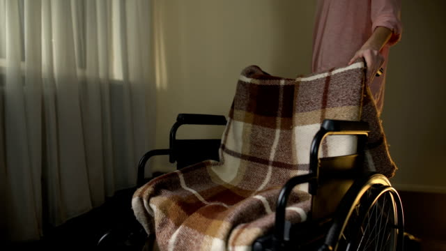Daughter-stroking-empty-wheelchair-with-sorrow-remembering-mother-passed-away