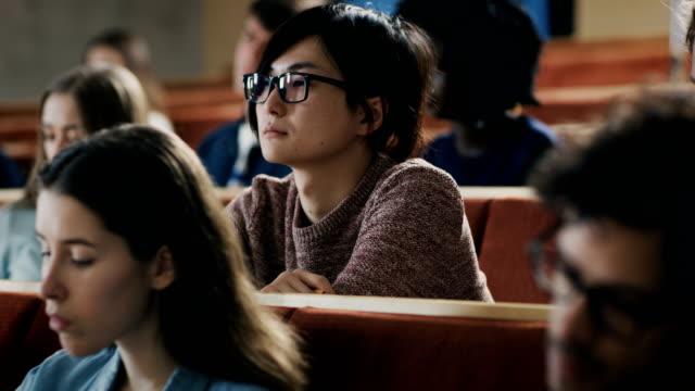 Gran-grupo-de-estudiantes-de-Multi-étnica-escuchando-una-conferencia-en-el-aula-Luminoso-estudio-en-la-Universidad-de-los-jóvenes-
