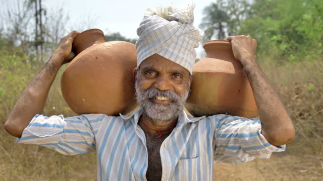A-happy-and-smiling-male-farmer-carrying-two-earthen-pots-filled-with-fresh-water-on-his-shoulders-in-countryside-