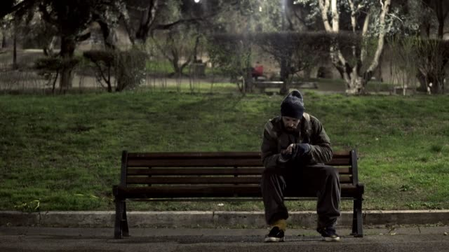 hungry-homeless-on-bench-at-night-counting-his-money