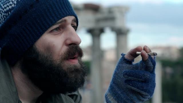 sad-and-thoughtful-homeless-man-lighting-a-cigarette