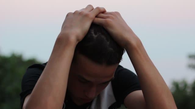Teen-Boy-Sits-Alone-Looking-Sad-Or-Worried