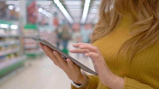 Female-customer-using-a-digital-tablet-at-supermarket