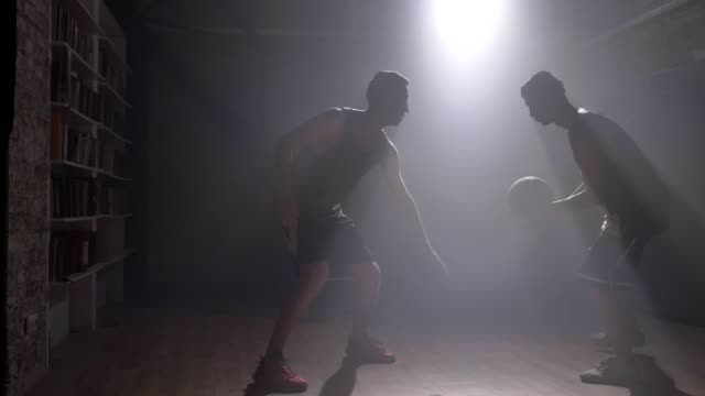 Two-friends-playing-basketball-indoors-man-giving-ball-to-other-player
