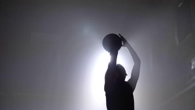 Basketball-Spieler-Silhouette-wirft-Ball-in-Reifen-Rauch-überall-Flutlicht-im-Hintergrund