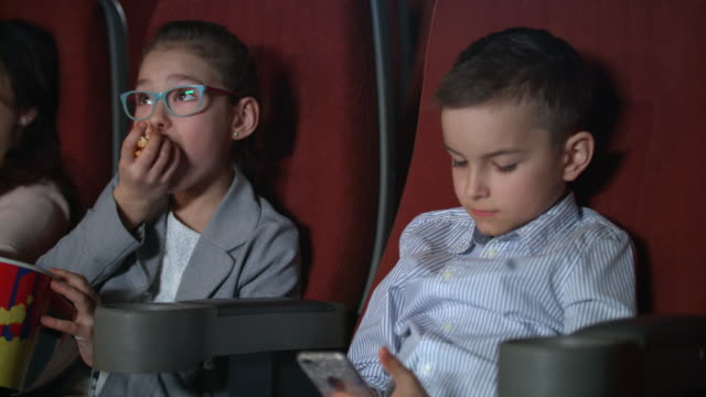 Little-girl-eating-popcorn-in-movie-theater-Boy-using-smartphone-at-cinema