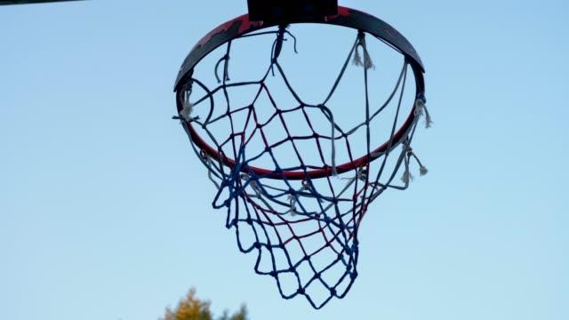 Lanzar-bola-en-el-aro-de-baloncesto-contra-el-cielo-azul-a-través-de-aro-al-aire-libre