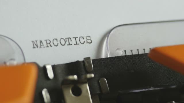Close-up-footage-of-a-person-writing-NARCOTICS-on-an-old-typewriter-with-sound