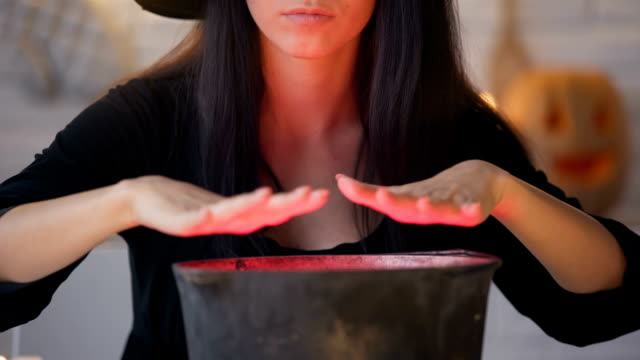 Young-witch-in-black-dress-conjuring-and-cooking-potion-Halloween-eve-magic
