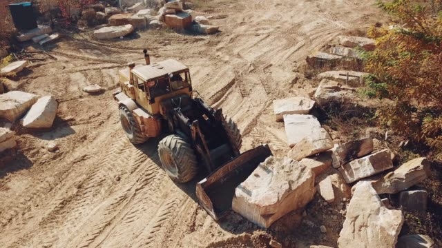 professional-equipment-with-a-bucket-is-turning-over-a-stone-and-raising-it-near-sandy-quarry-on-the-background-of-trees-