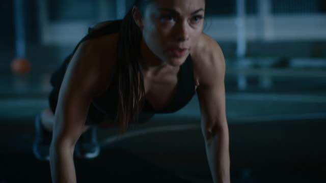 Gimnasio-deportivo-hermosa-chica-haciendo-Push-Up-ejercicios-Ella-está-haciendo-un-entrenamiento-en-una-cancha-de-baloncesto-al-aire-libre-cercado-Imágenes-de-la-noche-después-de-la-lluvia-en-una-zona-residencial-del-barrio-