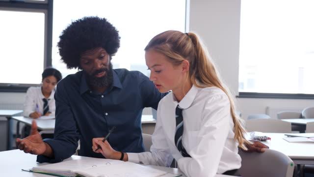 Tutor-de-secundaria-dando-estudiante-con-uniforme-enseñanza-uno-a-uno-en-el-escritorio-en-el-aula